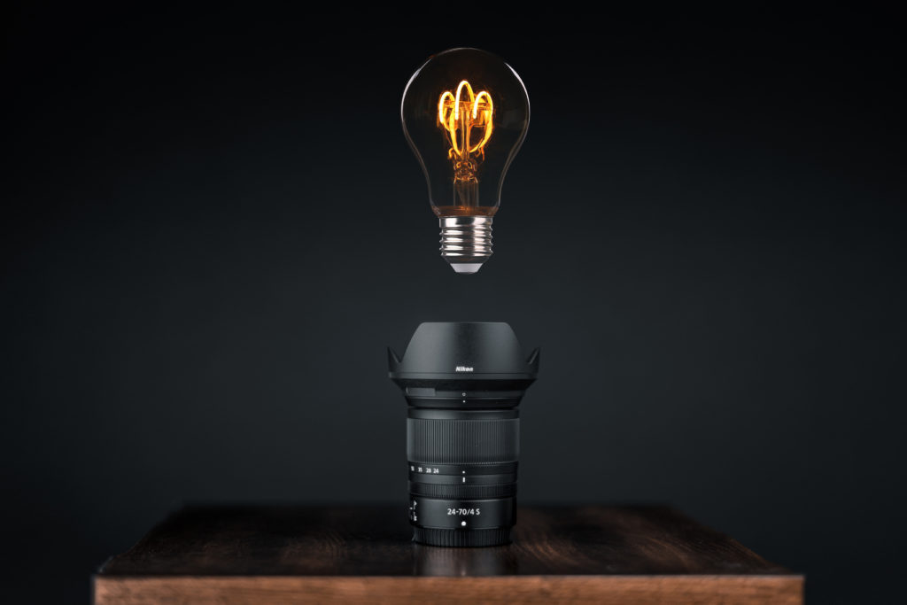 photographer's freedom - a camera lens on a table with a glowing light bulb hovering above it